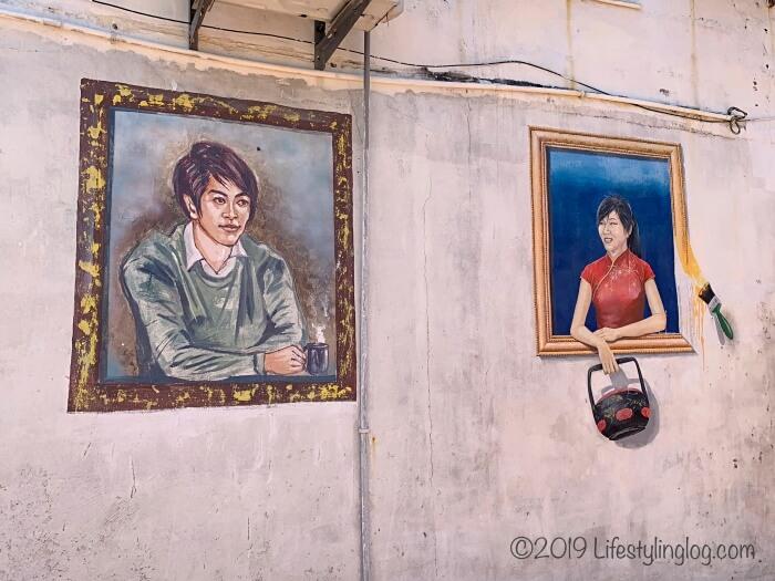 カップを持った男性とSia Basketを持った女性のストリートアート