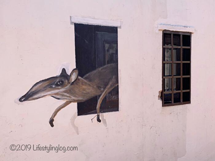 窓から動物が飛び出しているところを描いたマラッカのストリートアート