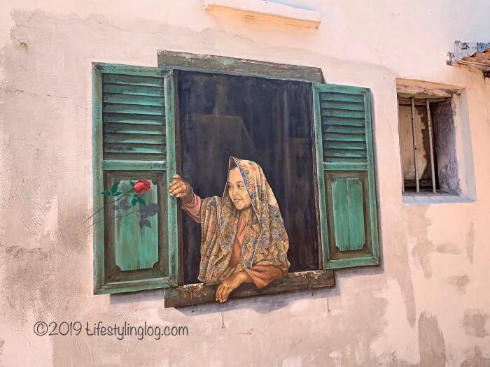 窓から顔を出す女性を描いたマラッカのストリートアート