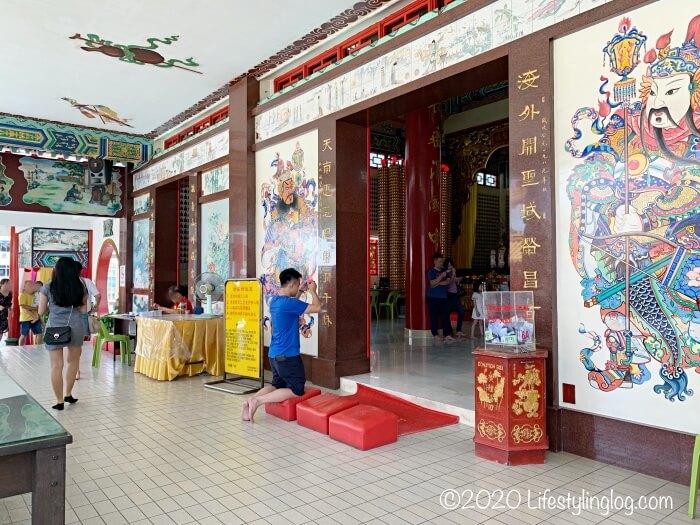 クアラルンプールの天后宮(Thean Hou Temple)の本殿前でお線香を持ってお参りしている男性