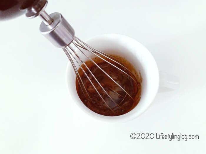 インスタントコーヒーと砂糖とお湯をハンドミキサーで混ぜているとこ