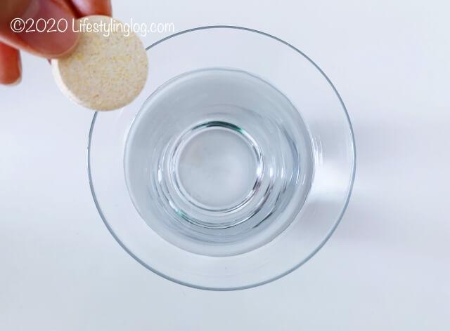 水が入ったグラスにBerocca(べロッカ)のビタミンタブレットを入れるところ